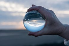 Hand holding a glass globe with reflections of a sunset